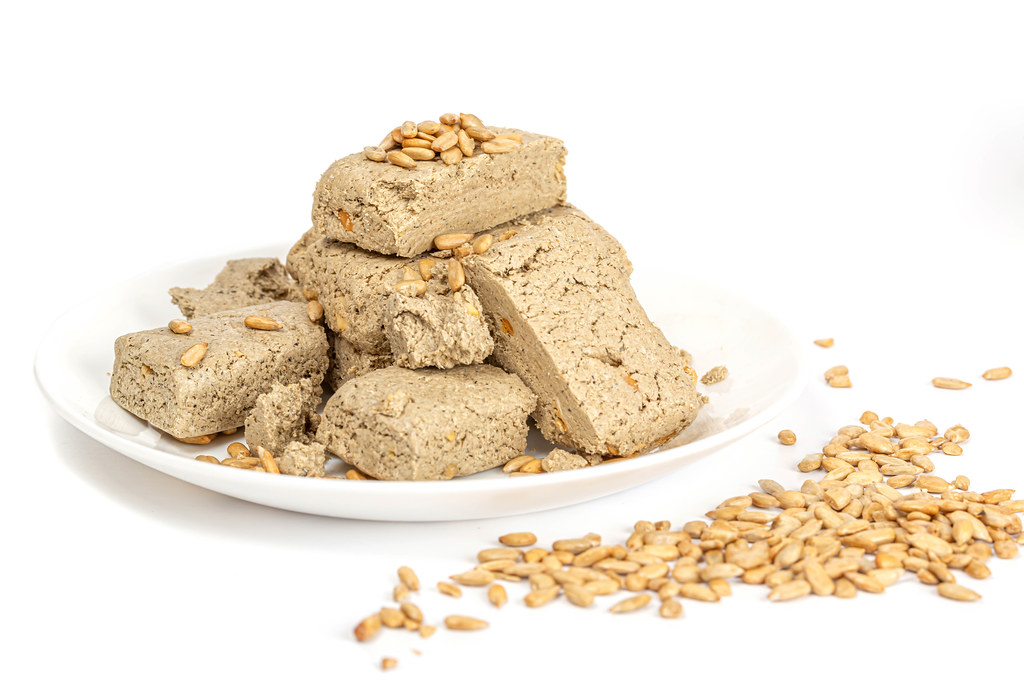Pieces of halva with nuts in plate on white