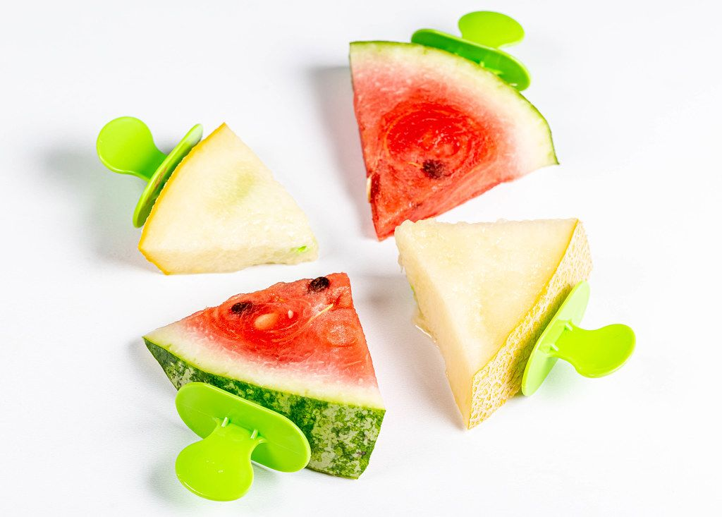 Pieces of ripe melon and watermelon on ice cream sticks
