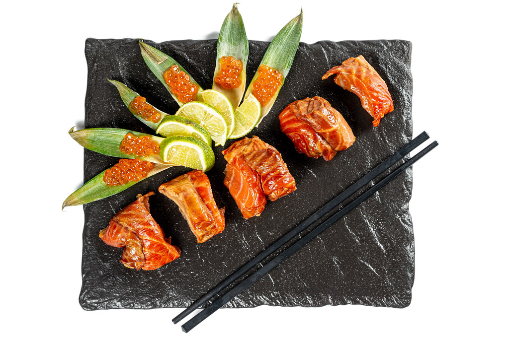 Pieces of smoked salmon with sliced lime and red caviar, top view