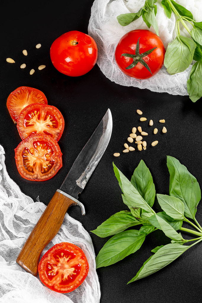 Pieces of tomatoes with basil branches, pine nuts and a knife on a dark background