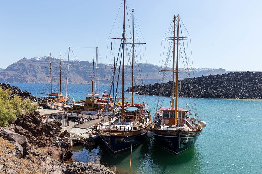 Pier in Santorini with four sailboats and the beautiful coast with cliffs in the background