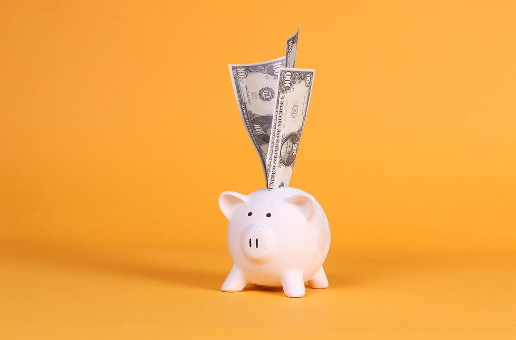 Piggy bank with dollar banknotes on orange background