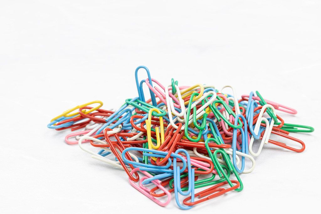 Pile of colorful Paper Clips above white background with copy space