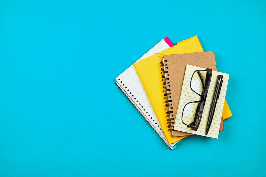 Pile of different notepads and diaries on blue background