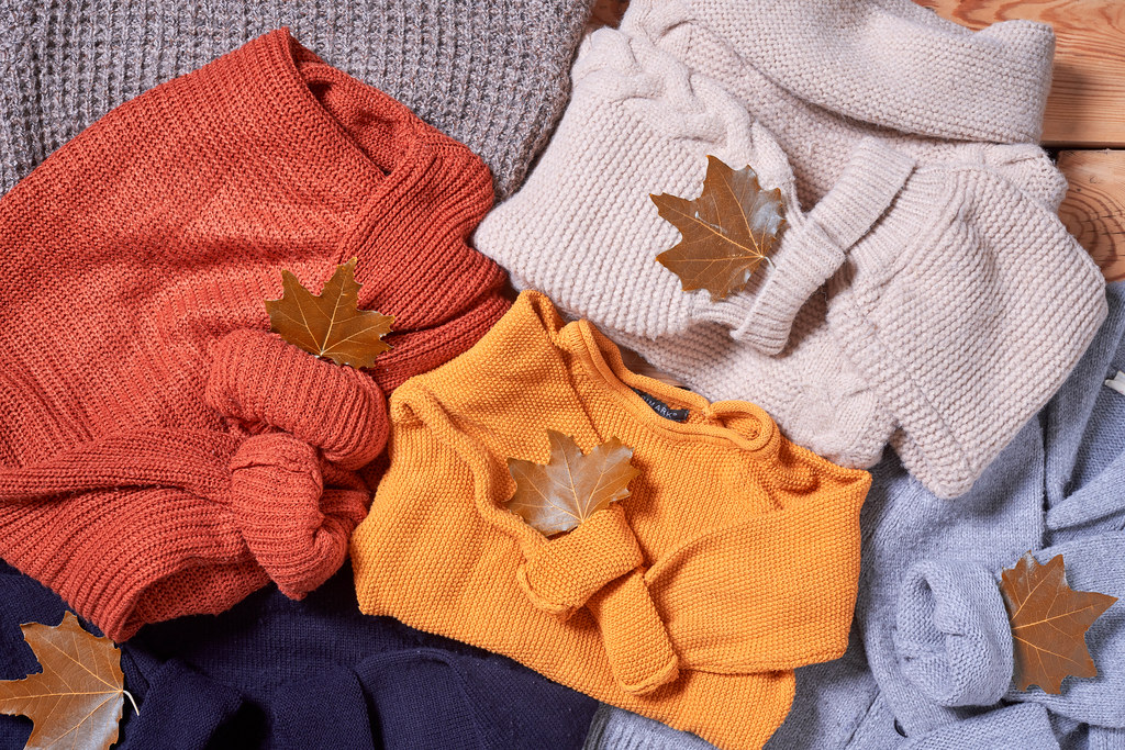 pile of knitted sweaters and fall leaves