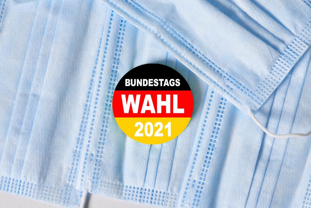 Pile of medical face masks and a pin in German flag. Bundestagswahl 2021