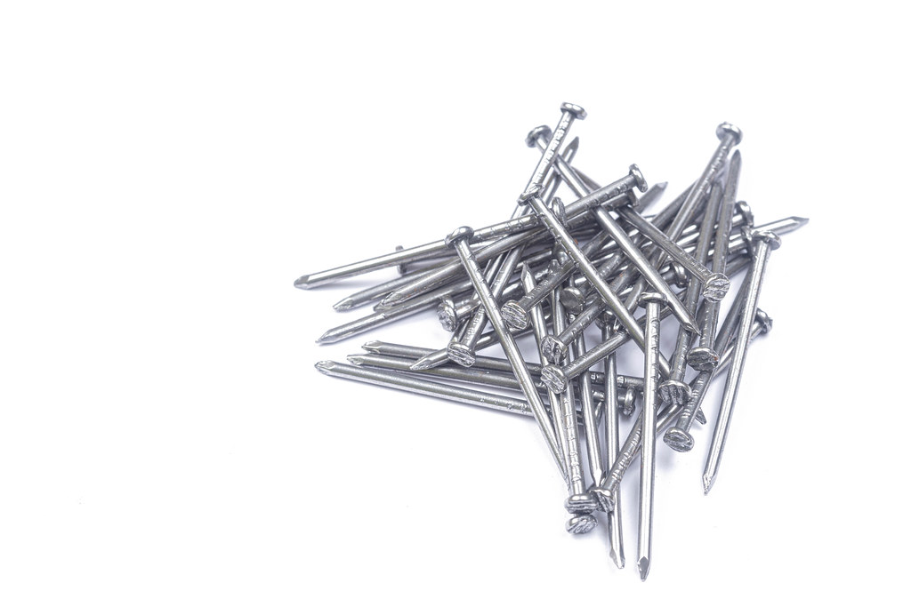 Pile of Nails above white background with copy space