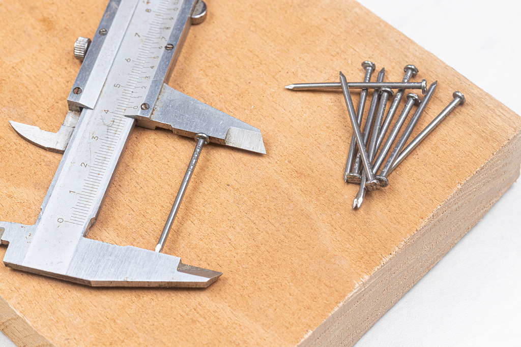 Pile of Nails on the wooden board with measuring caliper