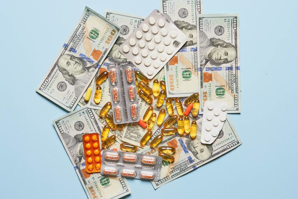 Piles of different medications and us dollars on blue background