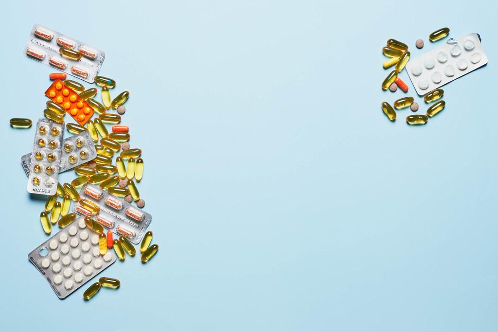 Pills and medical drugs on light blue banner background