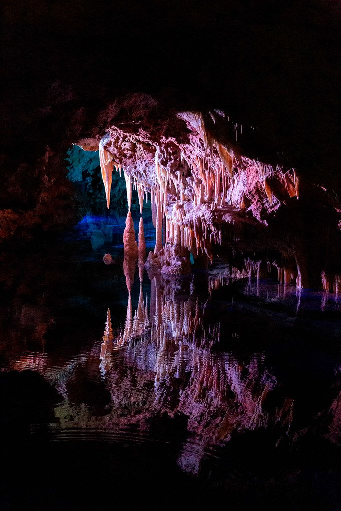 Pink lighting on the stalactites reflecting in the waters of the Sea of Venice, Cuevas del Hams caves