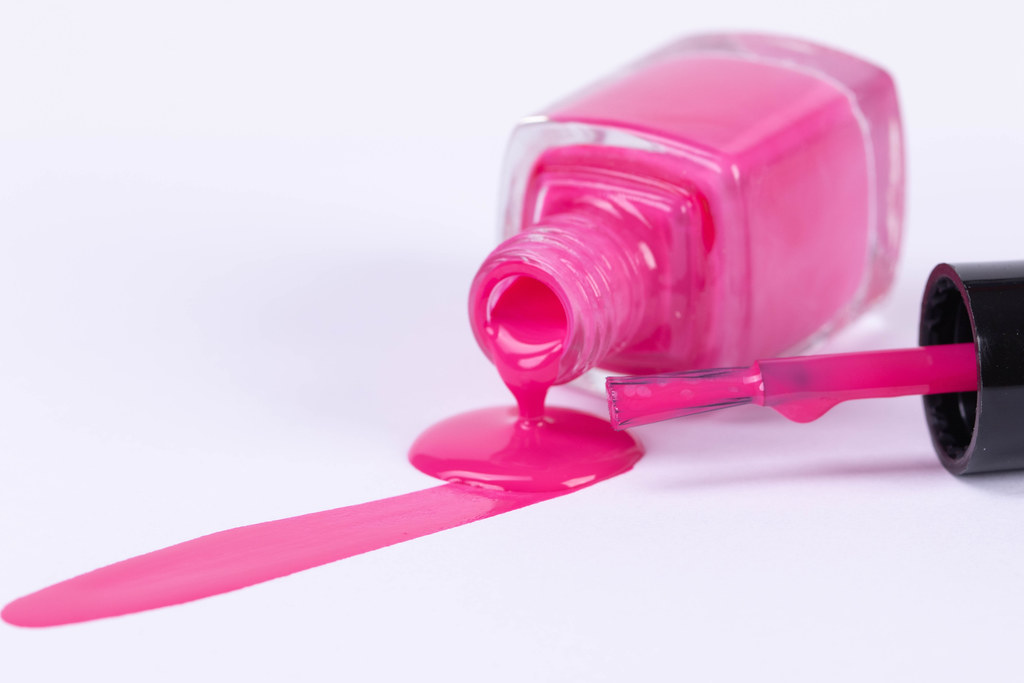 Pink nail polish spilled from the bottle with brush on white background