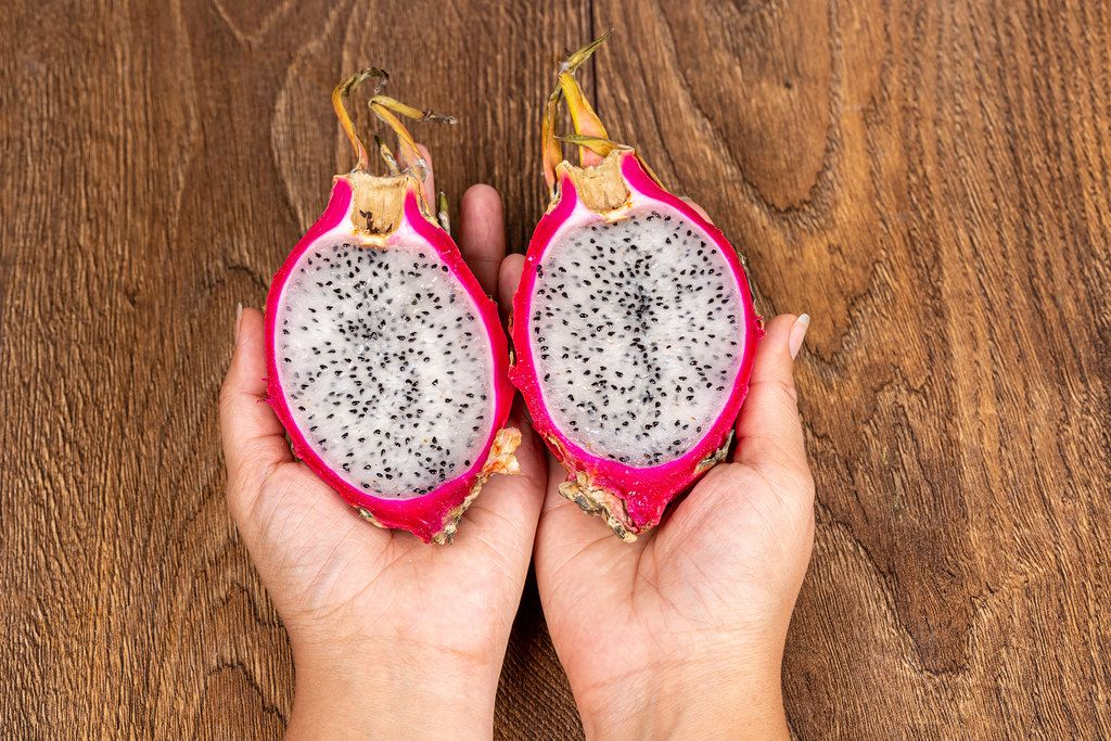 Pitahaya fruit halves in female hands on a wooden background, top view