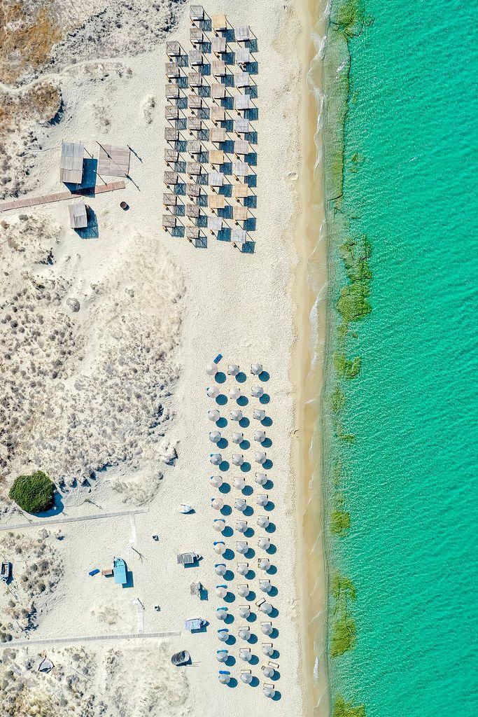 Plaka, Naxos. Drei Reihen runder Sonnenschirme aus Stroh und vier Reihen quadratischer Sonnenschirme