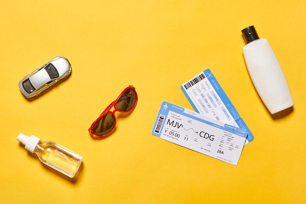 Planning summer vacations - flight tickets, anti-tan cream, hand sanitizer, sunglasses and miniature car model