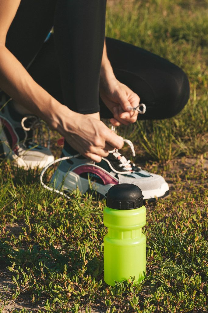 Plastic water bottle on the grass and female athlete preparing for jogging outdoors. Sport active lifestyle concept