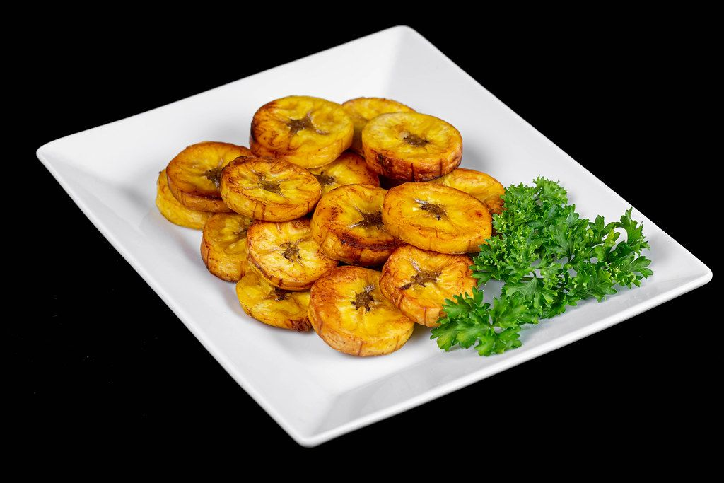 Plate with fried plantain and herbs on a black background
