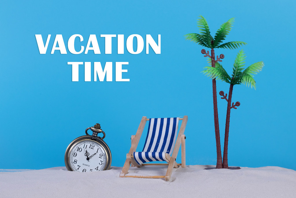 Pocket watch and beach chair with Vacation Time text on blue background