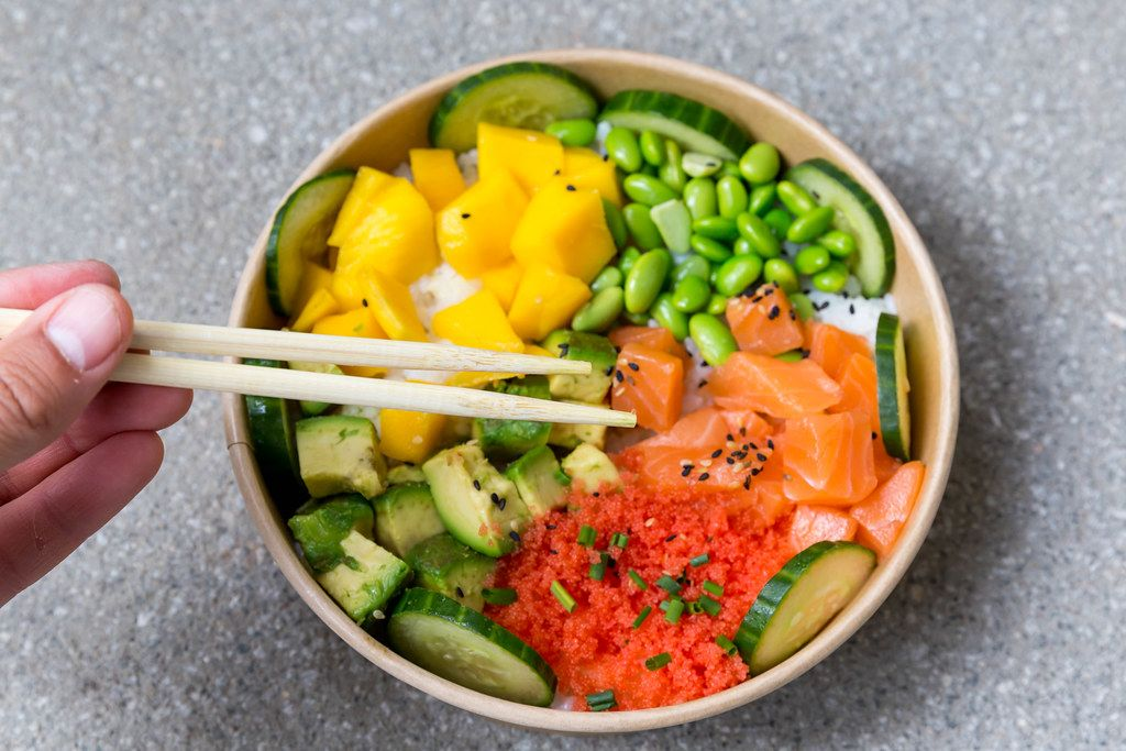 Poké bowl salmon: rice bowl with mango, masago, soybeans, vegetables. Eating with chopsticks