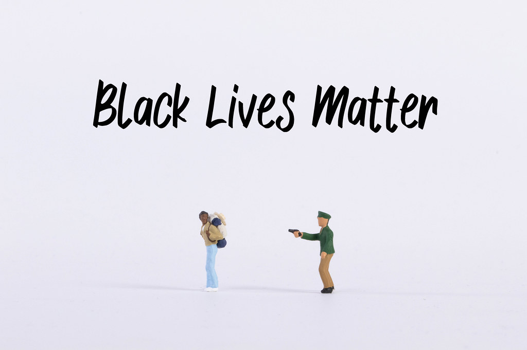 Policeman pointing a gun into a man with Black Lives Matter text