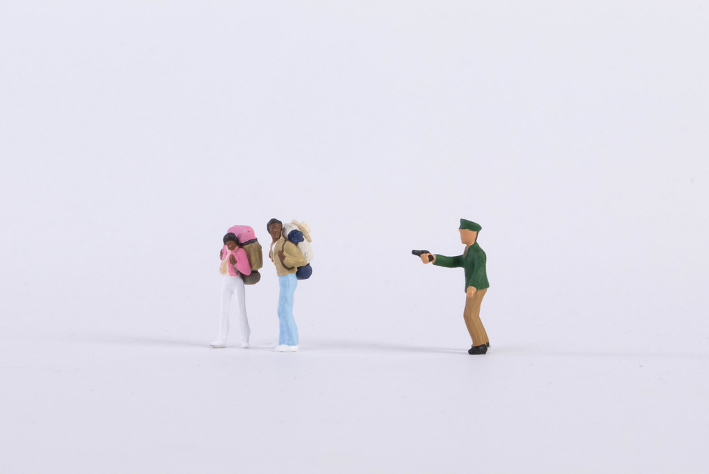 Policeman pointing a gun into two backpackers