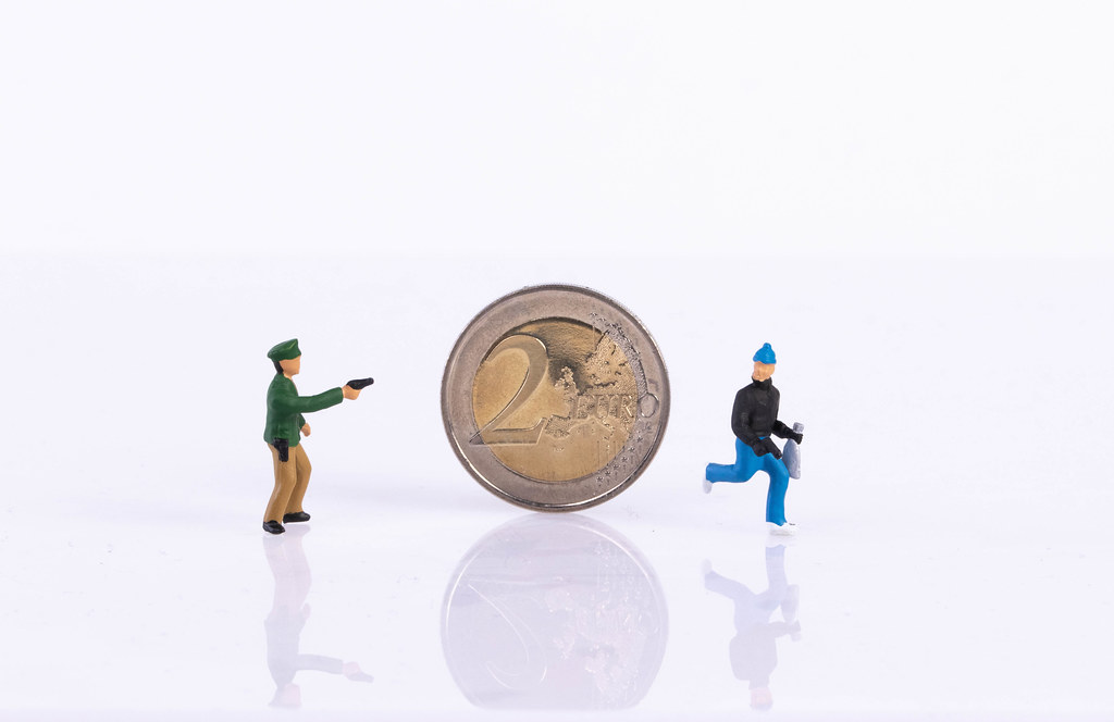 Policeman, robber and 2 Euro coin on white background