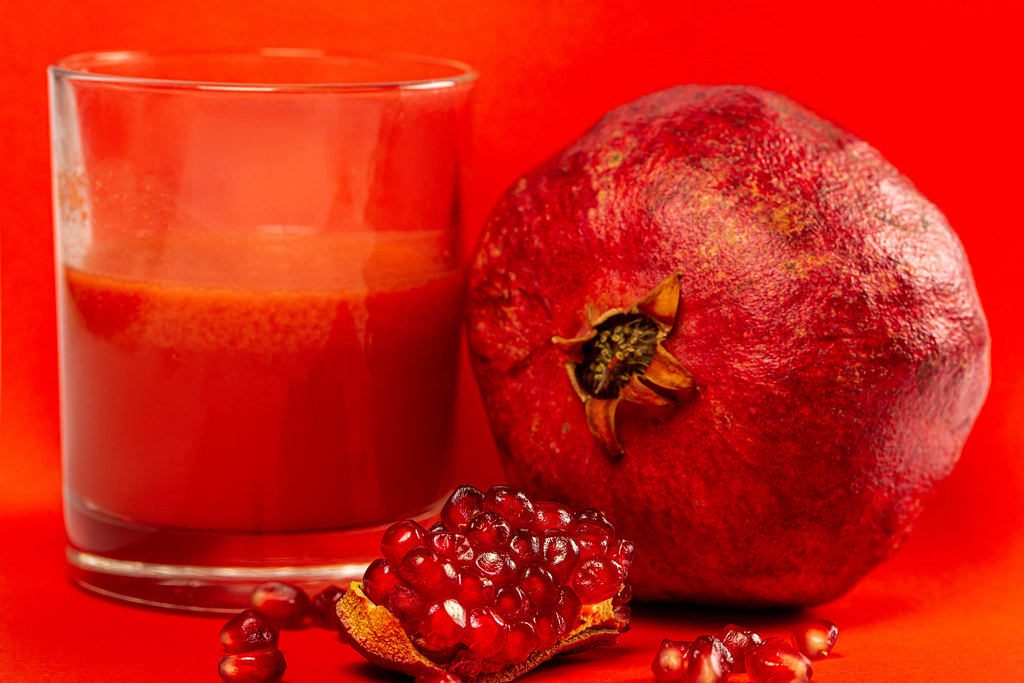 Pomegranate juice with fresh pomegranate on a red background