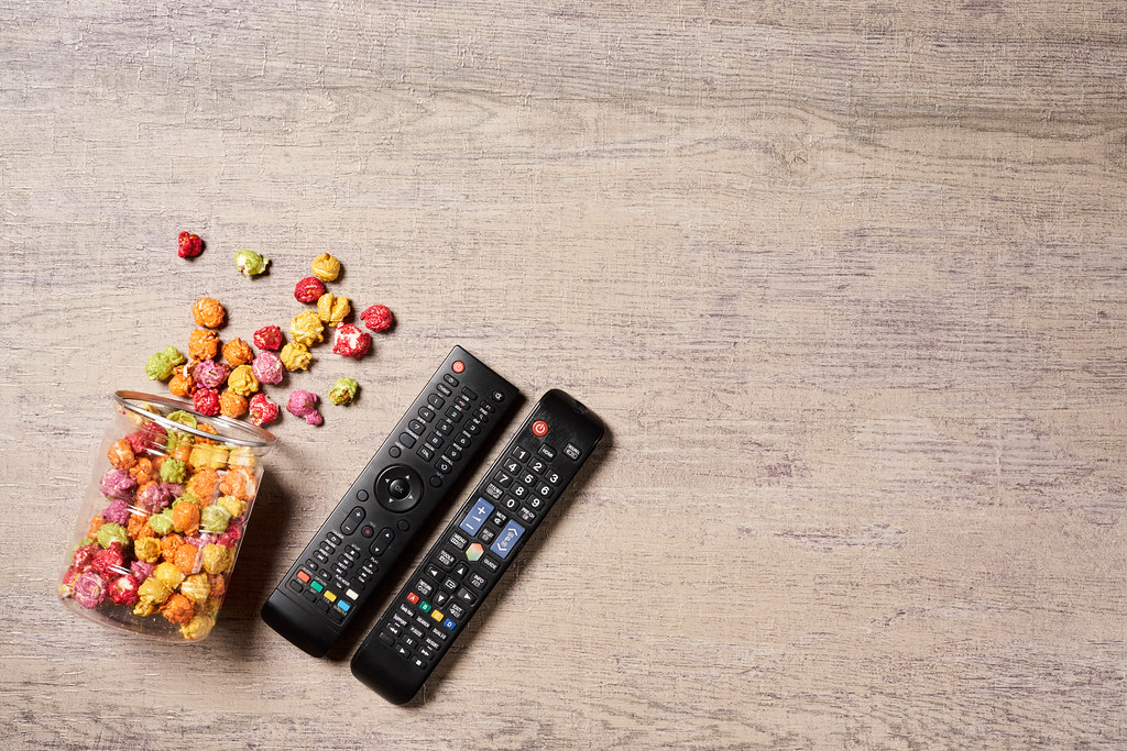 Popcorn and remote control for TV - leisure and entertainment of watching cinema