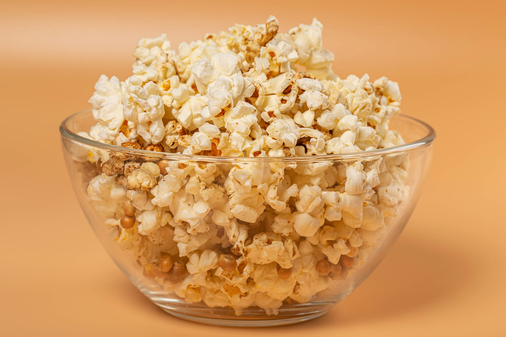 Popcorn in glass bowl on orange background
