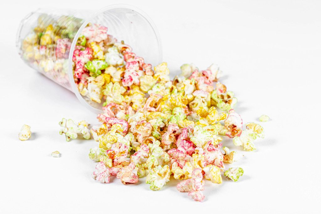 Popcorn scattered from a plastic cup on a white background
