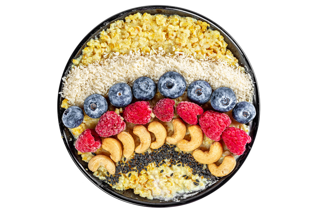 Porridge for breakfast with black sesame seeds, cashews, raspberries, blueberries and coconut on a white background, top view
