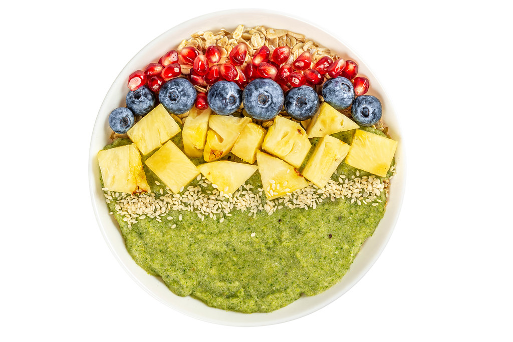 Porridge with blueberries, pomegranate, pineapple pieces, sesame seeds and green fruit puree on white, top view
