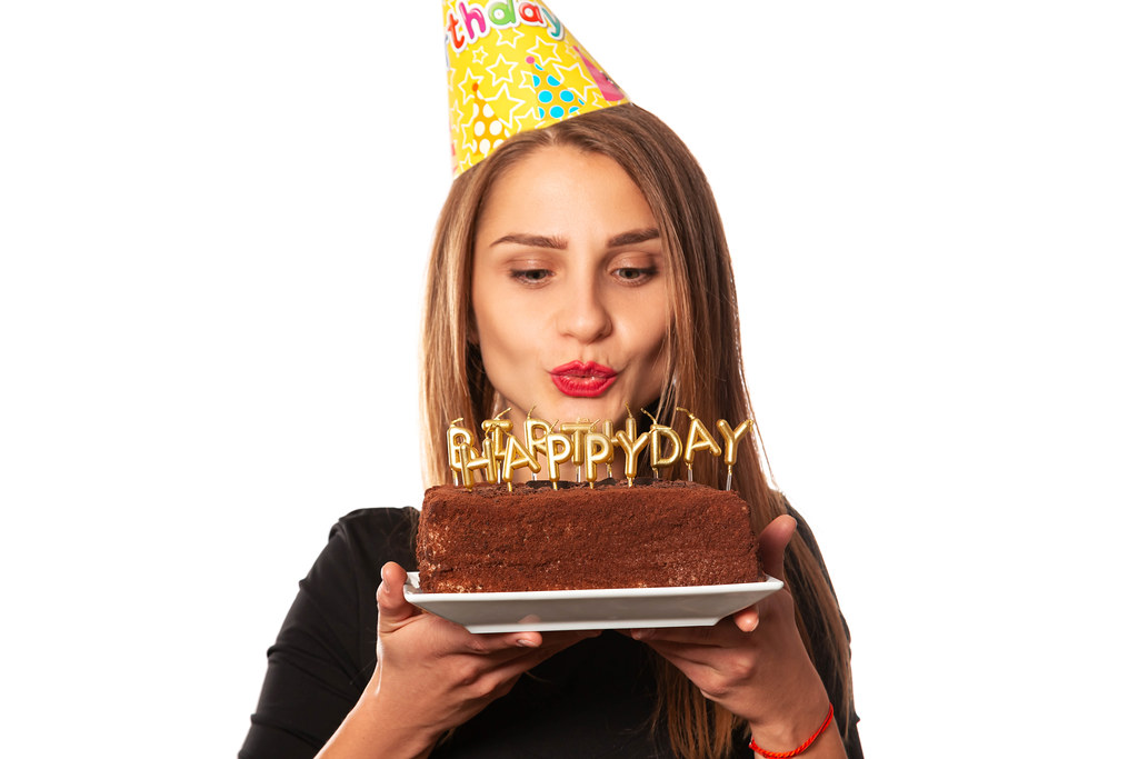 Portrait of beautiful girl wearing cone cap holding birthday cake with candles and making a wish