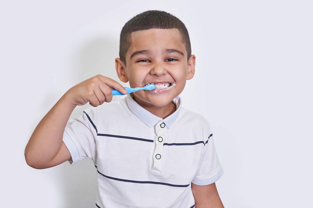 Portrait of little boy brushing teeth on light background