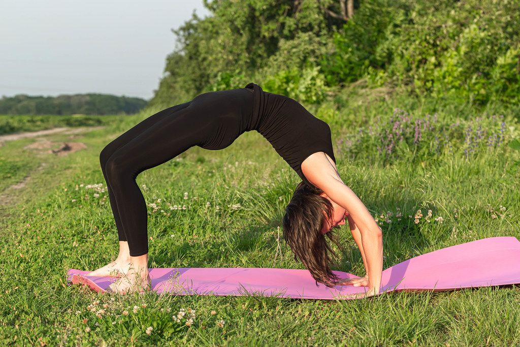 Pose of the bow face down - Urdhva Dhanurasana. Girl practices yoga