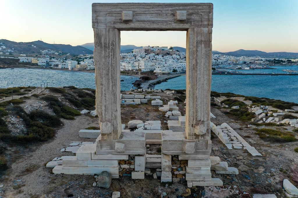 Postcard shot of Naxos with the marble gate of the incomplete Apollo temple framing the town of Chora