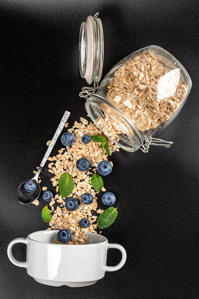 Poured oat flakes from a jar with fresh blueberries and mint on a dark background with a bowl and spoon