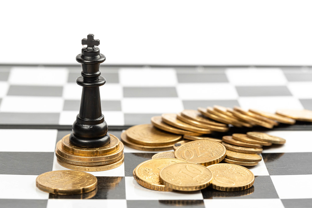 Power of the money concept - chess king standing on the money