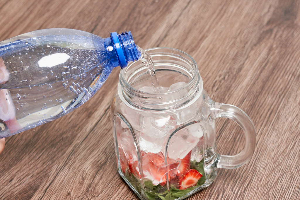 Preparing cold summer drink with fruits and soda