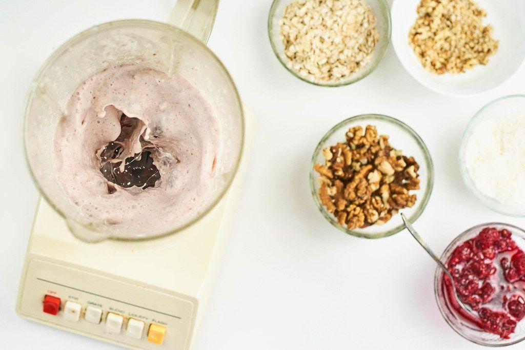 Preparing oats, walnuts, and raspberry based milkshake with blender