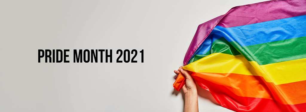 Pride month 2021 - LGBTQ+ activist holds a big rainbow flag