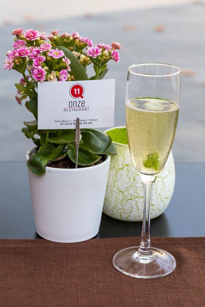 Prosecco Aperitif und Blumentopf auf dem Tisch beim Restaurant Q11 in Pollença, Mallorca
