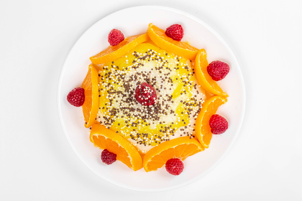 Pudding with fresh mandarin and raspberries, top view
