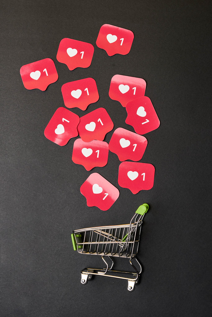 Purchasing paid promotion - shopping trolly and pile of Instagram love icons
