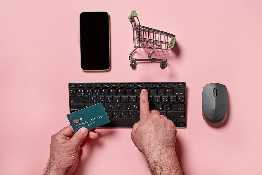 Purchasing products in online store - a man holding credit card and typing numbers on the keyboard