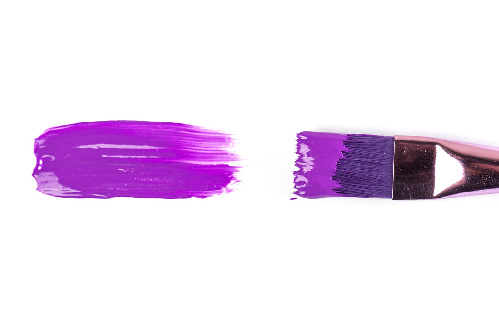 Purple paint with a brush on a white background