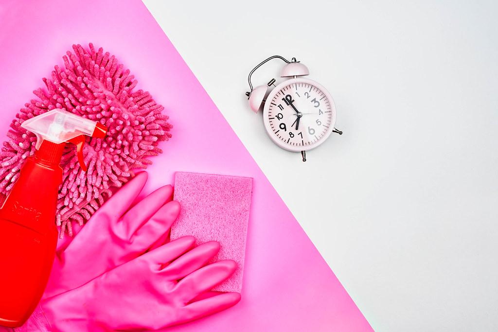 Putzen verschoben? Es ist nie zu Spät. Rosa und rote Reinigungsprodukte, Wecker und Platz für Text