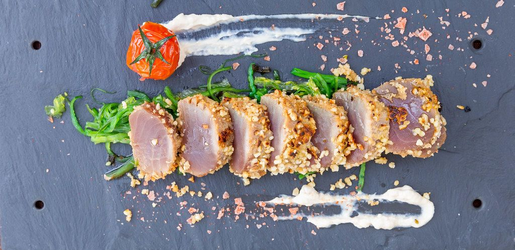 "Q11 restaurant in Pollença, Mallorca. Top view. Red tuna ""tataki"" in almond crust served with soya mayo"