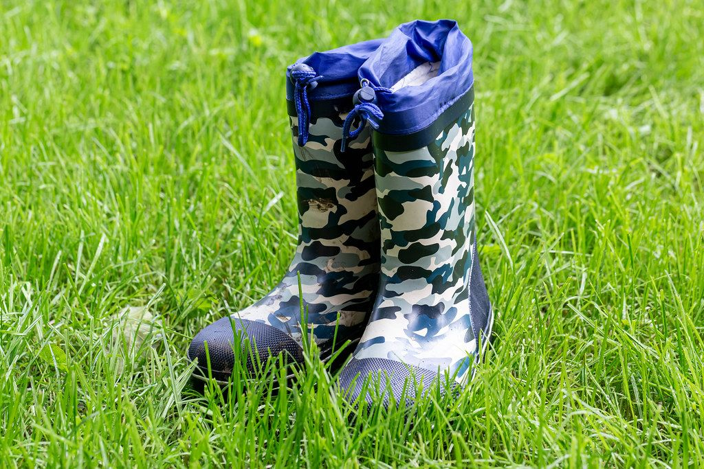 Rain boots for children on green grass