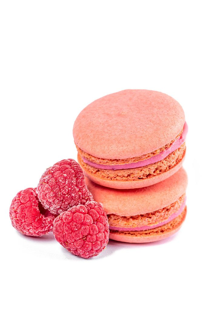 Raspberry macaroon cookies with berries on a white background